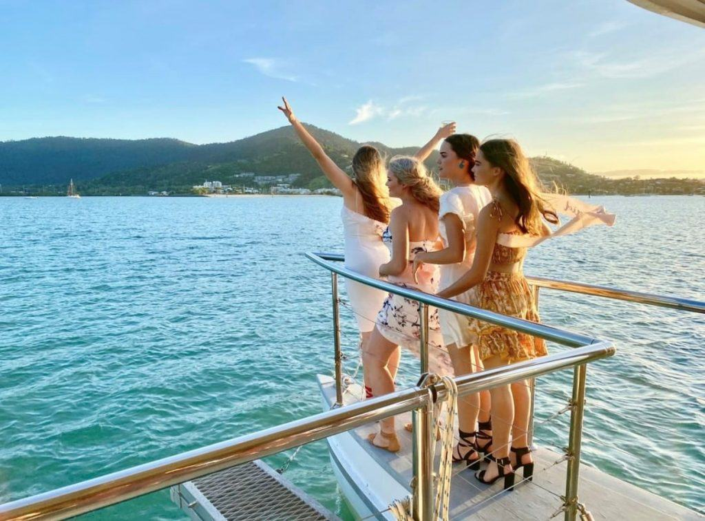 Group of women on the bow of Sundowner Cruises during a sunset cruise Airlie Beach