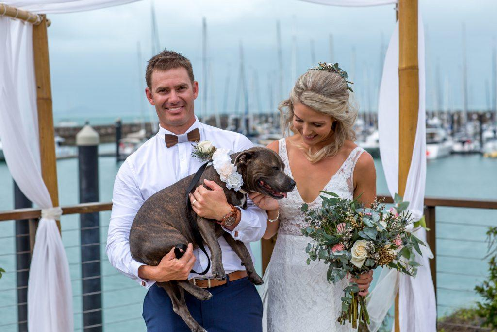 Wedding Photo of bride and groom with dog at a marina during wedding ceremony