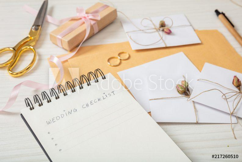 A wedding planner checklist with home made invitations wrapped in twine