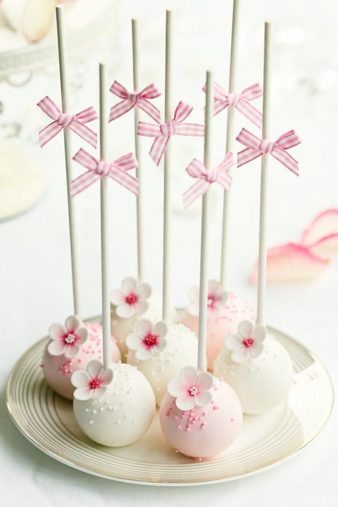 Plate of pink and white mini wedding cakes with bows